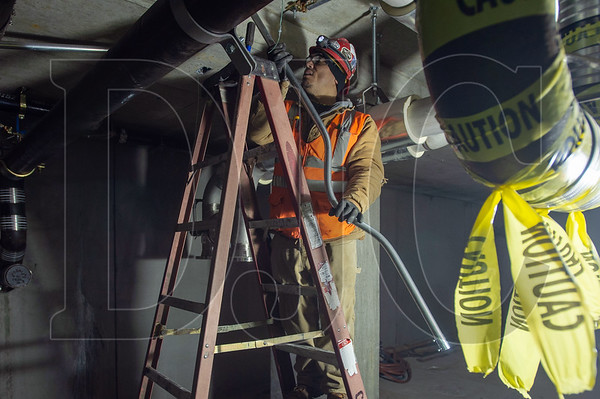 Joaquin Fuentes, a journeyman electrician with Local 48 and an employee of Cherry City Electric, installs conduit in a below-grade parking area at 5 MLK. (Josh Kulla/DJC)