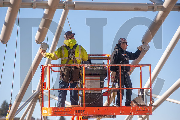 Eric Aldridge, left, and Jeff Barnes, both journeyman ironworkers with Local 29 and Carr Construction, secure a section of roof truss. (Josh Kulla/DJC)