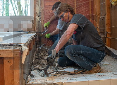 Jeanette Wagner, a journey level carpenter with Local 1503 and an employee of the Neil Kelly Company, demolishes tile at a remodeling project in Lake Oswego. Also pictured is Jon Hall, also a journeyman carpenter. (Josh Kulla/DJC)