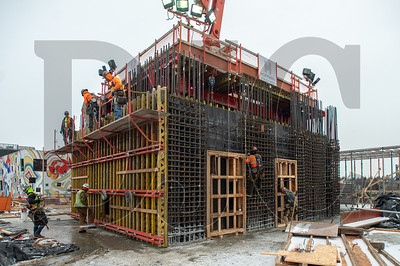 Carpenters with Hoffman Structures Inc., at left, construct formwork for the building's core while ironworkers from R2M2 Rebar, at right, build a rebar cage for the south wall. (Josh Kulla/DJC)