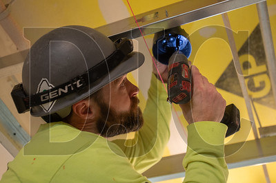 Craig Crum, a journeyman electrician with Bear Electric, installs a light fixture at Koz on 13th. (Josh Kulla/DJC)