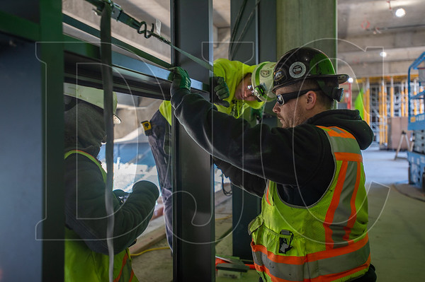 From left, Russell Walker,  Kyle Laheyne and Justin Belmore, all journeyman glaziers with Local 740 and employees of Encore Glass, install curtainwall. (Josh Kulla/DJC)
