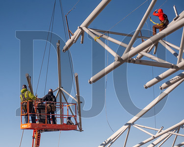 Ironworkers prepare to secure a roof truss as it lowered by a hydraulic crane. (Josh Kulla/DJC)