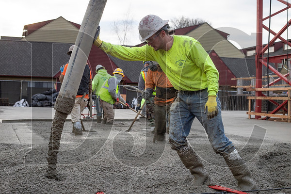 Tim Mathis, an apprentice finisher with Local 555 and employee of LaRusso Concrete, runs the nozzle during a concrete pour at Beacon Lake Oswego. (Sam Tenney/DJC)