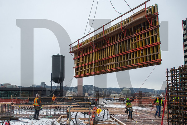 Carpenters with Hoffman Structures Inc. guide a steel formwork panel into place at 5 MLK, a 17-story mixed-use project under construction in Southeast Portland. (Josh Kulla/DJC)