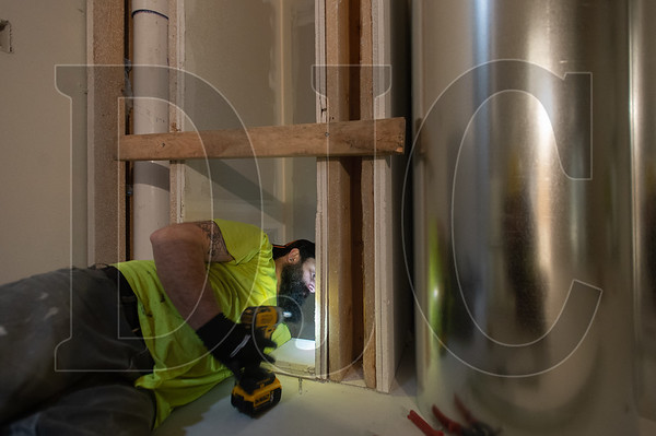 John Hall, a journeyman HVAC technician with Jacobs Heating and Air Conditioning, constructs an access chute for large laundry room exhaust ducts. (Josh Kulla/DJC)