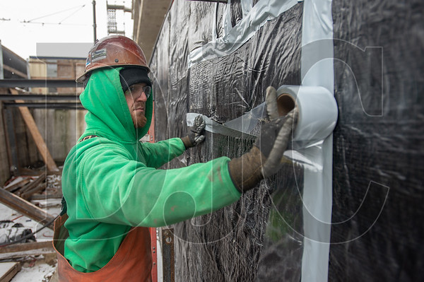 Jake Johnston, a journeyman pointer/cleaner/caulker with Local 1 and an employee of Pioneer Waterproofing, applies sealant tape to weather barrier on a below-grade wall. (Josh Kulla/DJC)