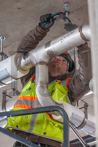 Apprentice plumber Dan Carpenter, a member of Local 290 and an employee of JH Kelly, tightens a pipe hanger for a water line. (Josh Kulla/DJC)