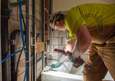 Kurt Morris, an apprentice plumber with Peninsula Plumbing, performs a leak test on a newly installed bathtub at the Williams Plaza building in Northwest Portland. (Josh Kulla/DJC)