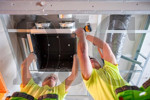 Tom Peabody, left, and Josh Ruggles, both journeyman HVAC technicians with American Heating, install ductwork. (Josh Kulla/DJC)