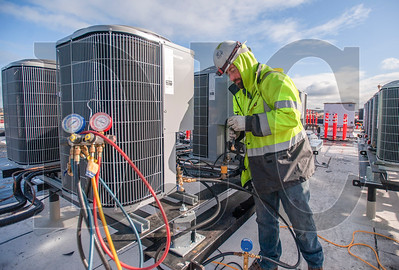 Matt Allen, a journeyman HVAC technician with American Heating, pressure tests a rooftop heat pump unit. (Josh Kulla/DJC)