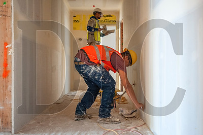 Westside Drywall installer Bernardo Hernandez Estrada applies mud to corridor wall. (Josh Kulla/DJC)