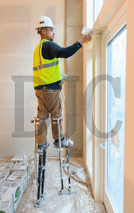 Jovanni Orantes, a drywall specialist with Westside Drywall, applies a skim coat of mud to the underside of a door frame. (Josh Kulla/DJC)