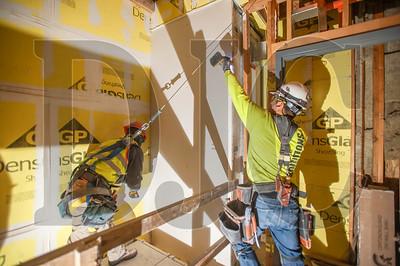Westside Drywall installers Sergio Ayala, left, and Esaias Valdez install drywall in the building's elevator shaft. (Josh Kulla/DJC)