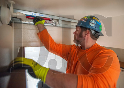 Paul Wilson, a journeyman sprinkler fitter with Local 669 and a crew foreman with Patriot Fire Protection, installs a fire sprinkler line at the doorway of a refurbished apartment. (Josh Kulla/DJC)