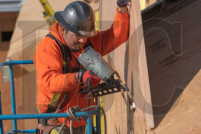 A carpenter with Time Frame Construction helps place a gable end on the roof. (Josh Kulla/DJC)