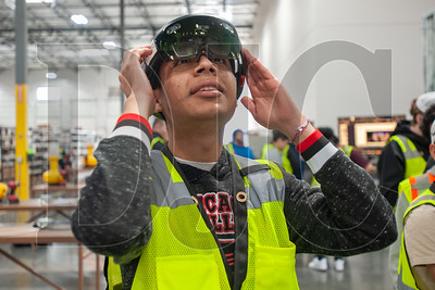 Aloha High School senior Juan Carlos dons a set of augmented reality glasses during a two-day School to Career program at Rosendin Electric's Hillsboro office. (Josh Kulla/DJC)