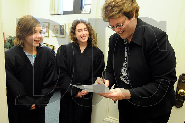 From left, Ava Ciccarello, 10, of Portland, and Abby Fellows, 10, of Happy Valley, receive tips from Multnomah County Circuit Court Judge Julie Frantz before taking the bench for a mock trial in Frantz' courtroom on April 28.