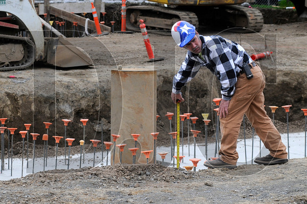 Dan Benderman, a plumber with Wolcott Plumbing, takes a measurement at the site of a 90-unit apartment building being constructed at the corner of Northwest 20th Avenue and Pettygrove Street in Portland on Friday.