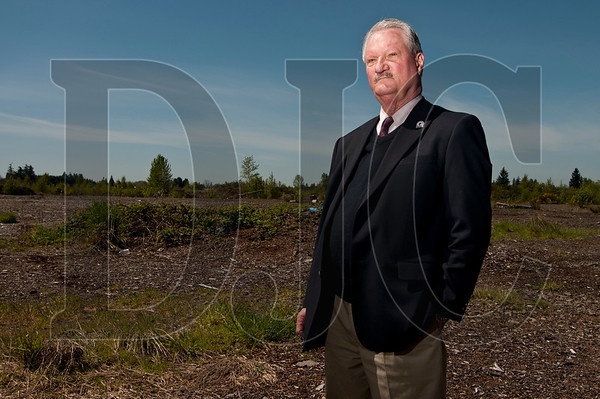 """Molalla City Manager John Atkins, Jr., stands on lot in the city where a mill once stood that he believes is ripe for redevelopment.  """"This is right in the heart of the city, so there's tremendous potential here for re-use,"""" said Atkins."""