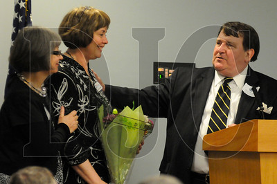 Jan Wierima, left, and Dick O'Connor, right, present Kathy Kollenburn, an administrative assistant for ACE Academy, with a bouquet of flowers during the OBC Awards Banquet & ACE Academy Showcase and Fundraiser in Portland on Tuesday.
