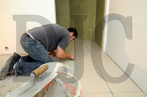 Vlad Koroteve, of New Millenium Construction, lays tile in a bathroom at the LifeQual Center in Beaverton on Thursday.