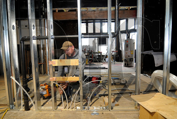 Hayden Talbot, a plumber with Mike Patterson Plumbing, works on the renovation of Voodoo Donut in Portland on Friday.