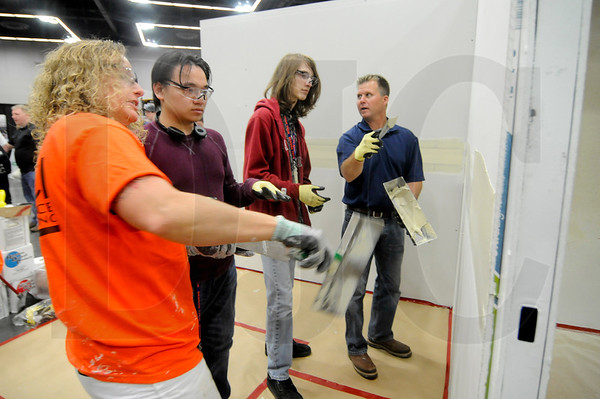 Benson Polytechnic High School juniors Johnny Trieu, second from left, and Quinn McCurdy, third from left, get a lesson in drywall finishing from Performance Contracting Inc. representatives Laurie Suchan, far left, a journeyman finisher, and Dave Holmquist, far right, a supervisor, during the NW Youth Careers Expo Tuesday at the Oregon Convention Center.