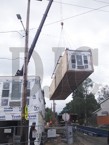 One of the final modular units of the Dekum 13 project is craned into place Friday in Northeast Portland. Manufacturer Guerdon Modular Buildings built the three-story, 28-unit apartment building for developer Northwest Ventures Group. (Garrett Andrews/DJC)