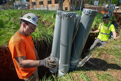 Michael Stewart, left, and Danil Rybalka, both electricians with Advanced Electric, place below-grade conduit. (Josh Kulla/DJC)