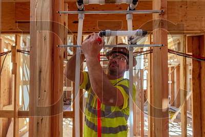 Josh Hadley, a plumber foreman with Tapani Plumbing Inc., installs water lines at the Pleasant Avenue Veterans Housing project in Oregon City. (Josh Kulla/DJC)
