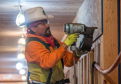 Juan Ledesma installs particle board sheathing in an interior corridor. (Josh Kulla/DJC)