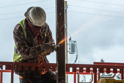 Chase Foster, an apprentice ironworker with Steel Management Services, grinds the edge of a bracket. (Josh Kulla/DJC)