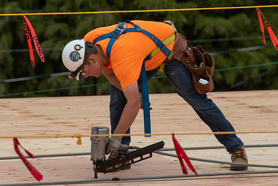 A carpenter with Wood Mechanix installs plywood sheathing on the roof of the office portion of the building. (Josh Kulla/DJC)