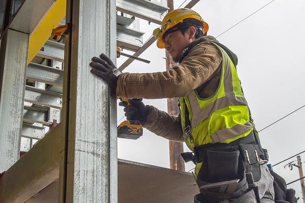 Apprentice carpenter Huy Hoang of B&I Construction frames a ground-floor storefront. (Josh Kulla/DJC)