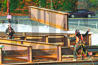 Ironworkers on the Sellwood Bridge replacement project lower a 50-foot girder, which will be used to support the temporary detour bridge, into place on the project's west side Thursday.