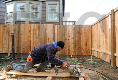 Abel Ortega, an employee of Scholls Farm & Nursery Inc., cuts wood while builing a fence on a pair of new homes built by Renaissance Homes in Northeast Portland. According to Randy Sebastian, president of Renaissance Homes, the company has seen a 100 percent increase in sales and closings this year.