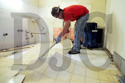 Chris Knowles, an employe of Laneco Inc., removes linoleum from an apartment in the 1200 Building in downtown Portland Tuesday. General contractor R&H Construction is performing a $26 million rehabilitation of the building, a 10-story affordable housing complex for senior citizens.