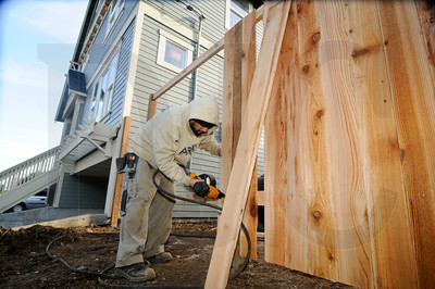 Raoul Vargas, an employee of Scholls Farm & Nursery Inc., installs a fence at a new home built by Renaissance Homes in Northeast Portland Thursday. According to the Associated General Contractors of America, residential building has risen 21 percent thus far in 2012 and is expected to continue to grow in 2013.