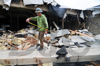 Jeff Wagner measures a downed beam in preparation for transporting it offsite.