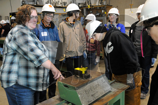 Allie Medeiros, left, a journeyman sheet metal worker, shows students how to operate a roll forming machine.