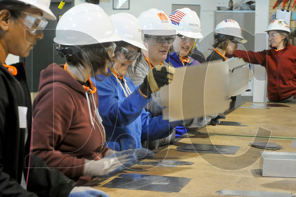 Students gather around a work bench in a shop at the Sheet Metal Institute to start a project making a metal box.