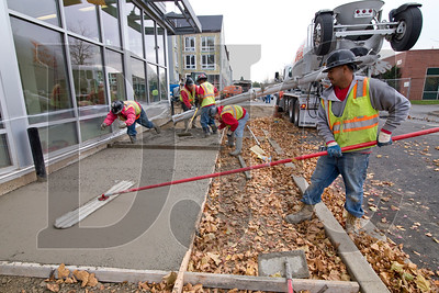 Nestor Avila, right, a concrete finisher with Roger Legeliers Construction Co., smoothes a freshly-poured sidewalk.
