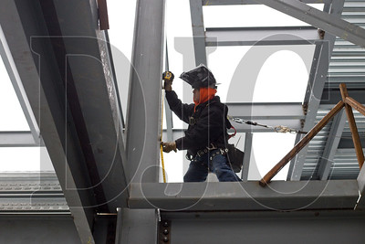Marvin Archuleta, an ironworker with A36 Structures, takes a measurement before while installing a cable fall protection system.