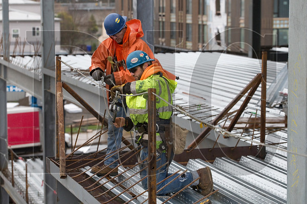 Ian Stafford, left, and Dane Wilkerson, both ironworkers with A36 Structures, tension cable while installing a fall protection system.
