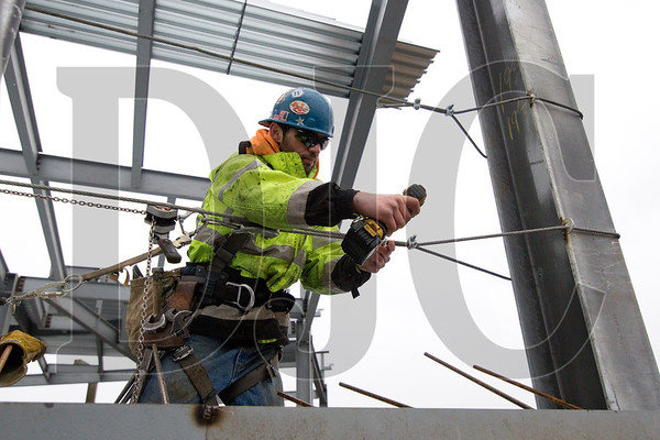 Dane Wilkerson, an ironworker with A36 Structures, tightens a third-floor fall protection cable.