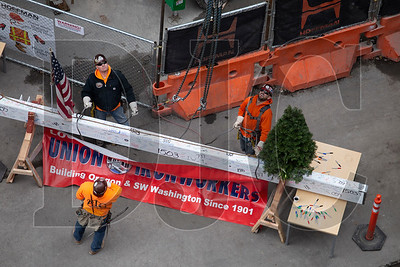 Union ironworkers with Alliance Industrial Group wait for the hook to be lowered before rigging the beam.