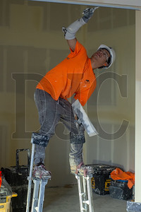 Mario Mecio, a journeyman drywall finisher with IUPAT Local 10 and an employee of Anning Johnson Company, applies drywall plaster inside the library portion of the project.