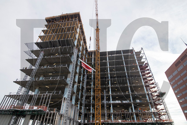 The beam is hoisted up on the building's west side along Southwest First Avenue.