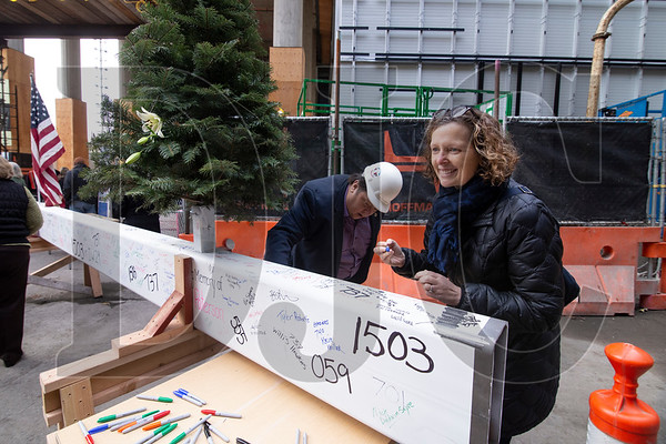 Liz Smith Currie, right, senior policy advisor for Multnomah County Chairwoman Deboray Kafoury, and Willie Myers, executive secretary treasurer of the Columbia Pacific Building Trades Council and a Prosper Portland board member, sign the beam before the start of the ceremony.